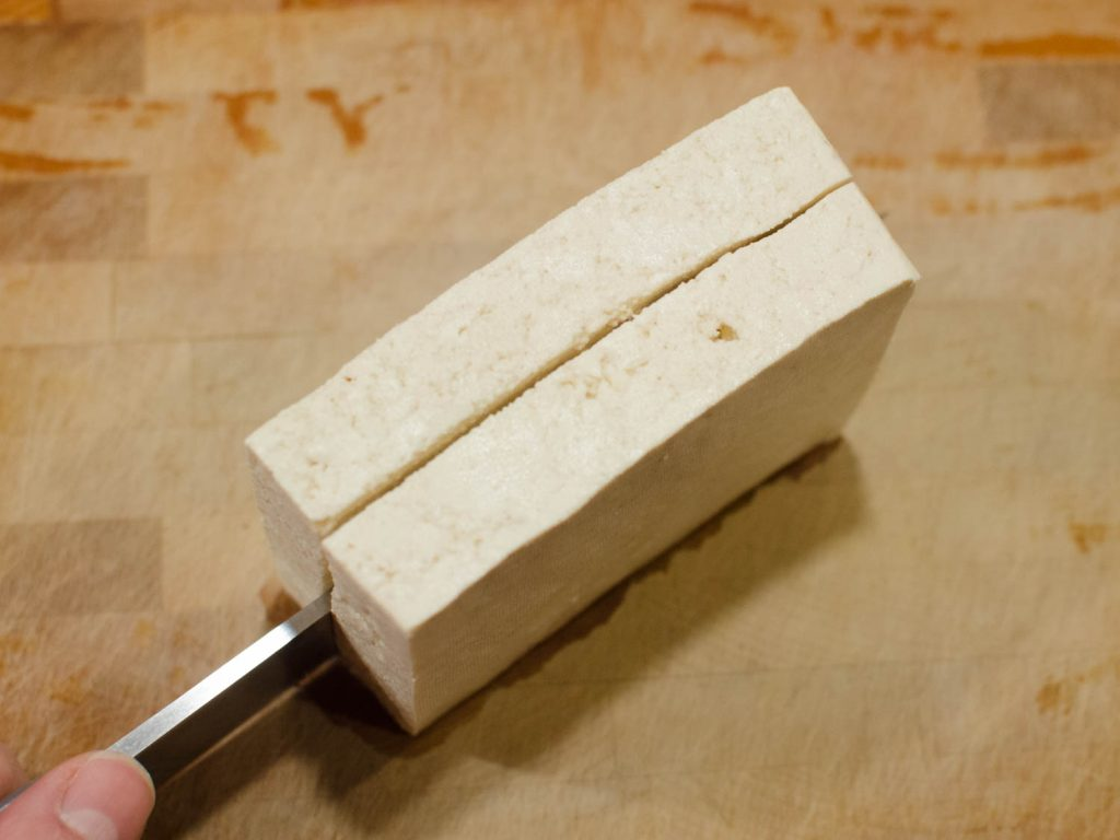 Extra Firm Tofu being sliced in half