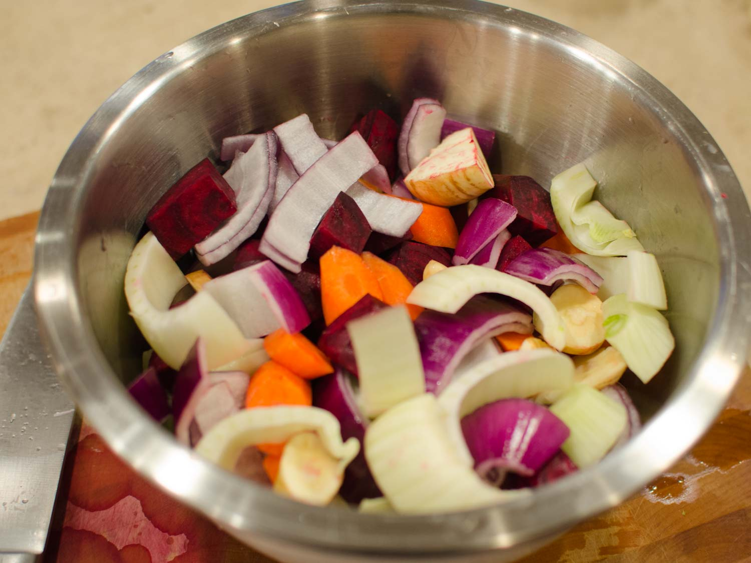 Mixing bowl with red beets, fennel, parsnip, carrots, red onion and garlic tossed with Olive Oil
